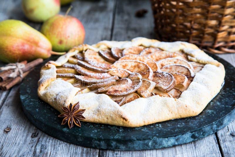 Empanada con las manzanas, las peras y el canela en un viejo fondo de madera foto de archivo