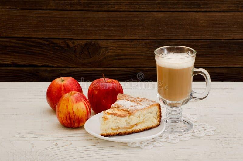 Empanada de Apple, capuchino y manzanas maduras en un fondo de madera fotos de archivo libres de regalías