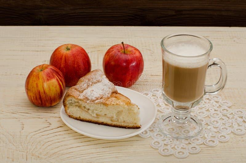 Empanada de Apple, capuchino y manzanas maduras en una tabla de madera imagen de archivo