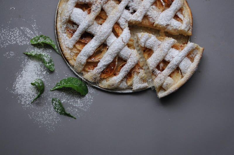 Empanada de Apple en fondo gris Postre Torta hecha en casa Otoño flatlay Pedazo de torta hecho en casa con el polvo de la menta y fotografía de archivo libre de regalías