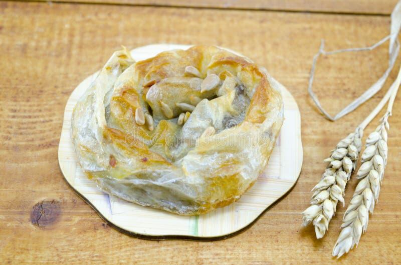 Empanada de carne sabrosa con las semillas en una tabla de madera fotografía de archivo libre de regalías