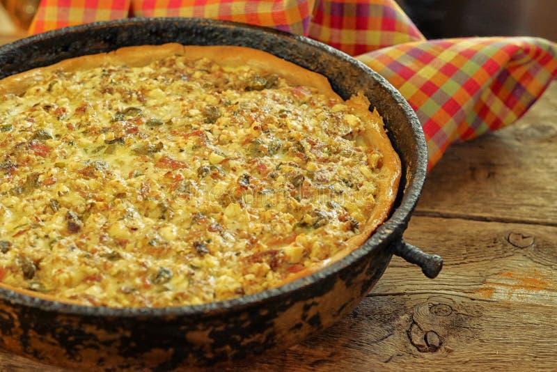 Empanada de la quiche con el pollo, la pimienta verde, el jamón y la seta en blac foto de archivo