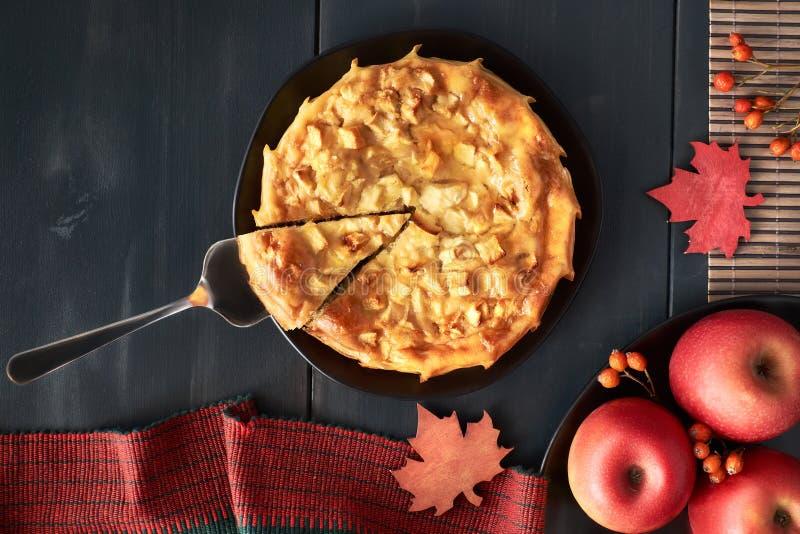 Empanada de manzana hecha en casa en la placa oscura con las manzanas en fondo oscuro imagen de archivo