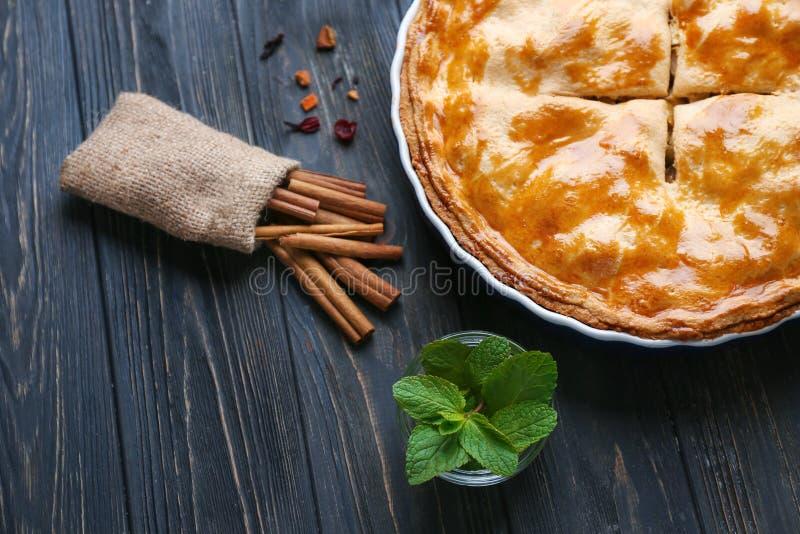 Empanada de manzana hecha en casa sabrosa con la menta y el canela en la tabla de madera foto de archivo libre de regalías