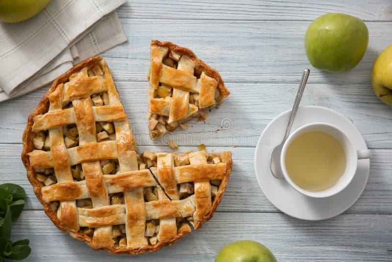 Empanada de manzana y taza hechas en casa sabrosas de té en la tabla de madera imagen de archivo libre de regalías