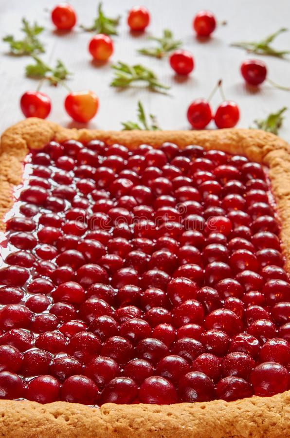 Empanada deliciosa de la cereza con la jalea en el fondo gris de la cocina Tarta fría hecha en casa de la cereza adornada con las fotografía de archivo
