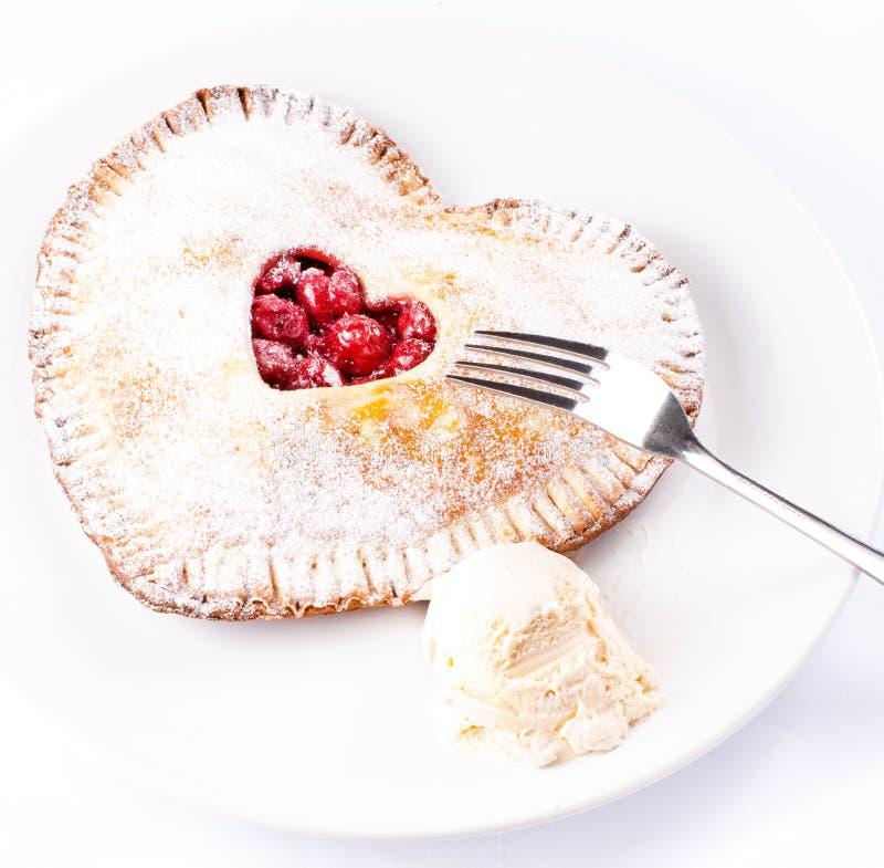 Empanada en forma de corazón de la cereza con helado de vainilla en blanco imágenes de archivo libres de regalías