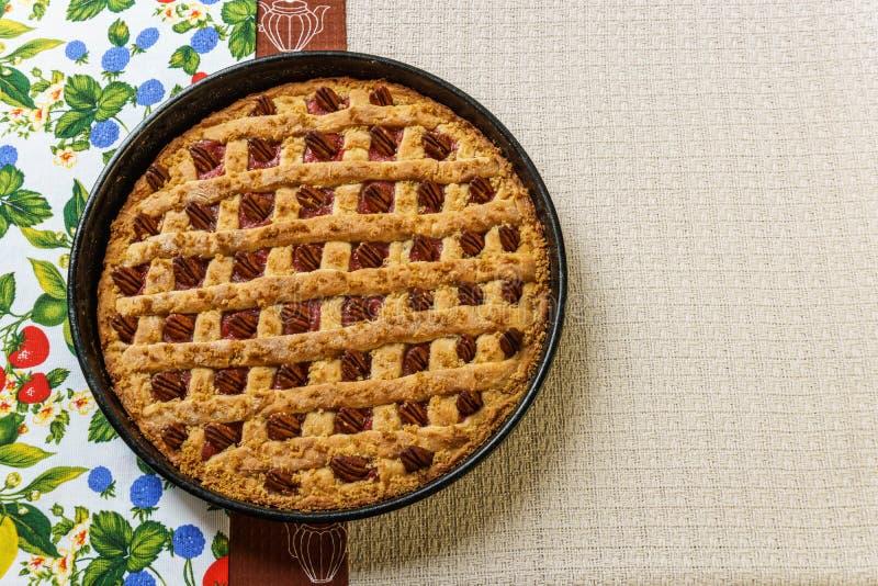 Empanada entera de la manzana y de ruibarbo con la pacana en una bandeja negra en una tabla fotografía de archivo