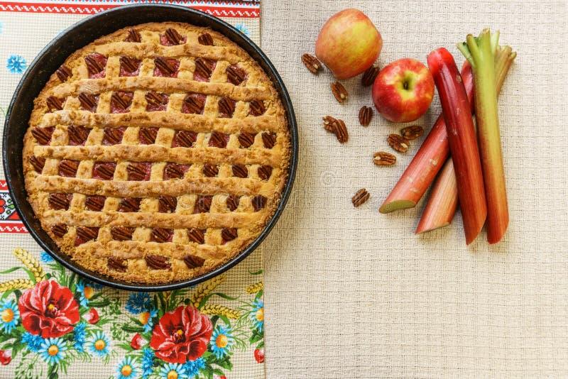 Empanada entera de la manzana y de ruibarbo con la pacana en una bandeja negra en una tabla fotos de archivo
