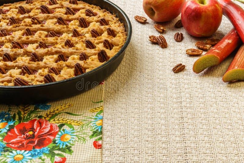 Empanada entera de la manzana y de ruibarbo con la pacana en una bandeja negra en una tabla imagen de archivo libre de regalías