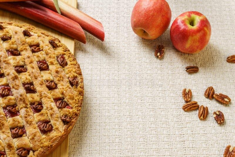 Empanada entera de la manzana y de ruibarbo con la pacana en una bandeja negra en una tabla fotografía de archivo libre de regalías