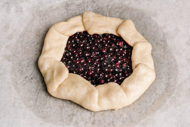 Empanada hecha en casa del galette con las grosellas rojas y negras, los arándanos y las frambuesas en fondo de madera fotos de archivo