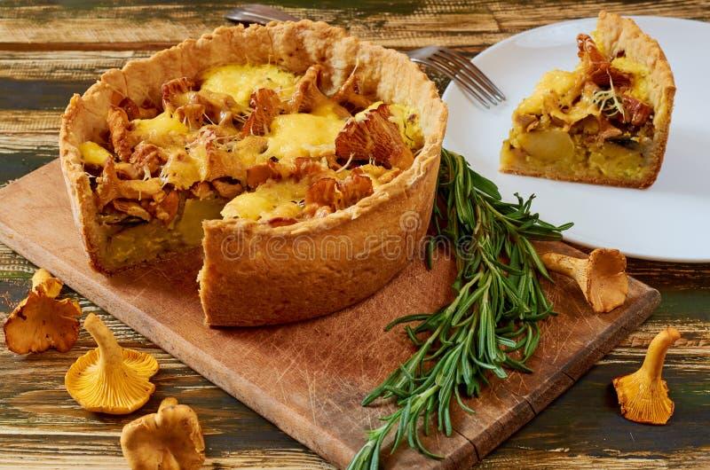 Empanada sueca del queso y de la seta - quiche en la tabla de cocina adornada con romero Mízcalos vegetarianos cortados agrios fotografía de archivo libre de regalías