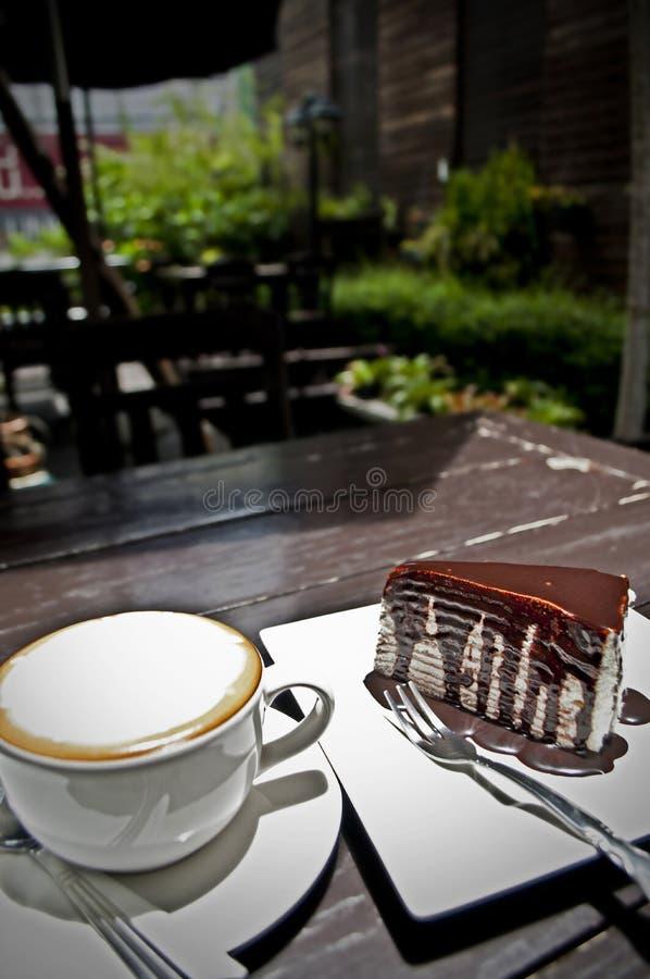 Empanada y capuchino del chocolate en una tabla de madera en un jardín imagenes de archivo