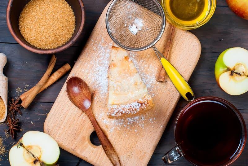 Empanada y té de Apple en una tabla de madera fotos de archivo