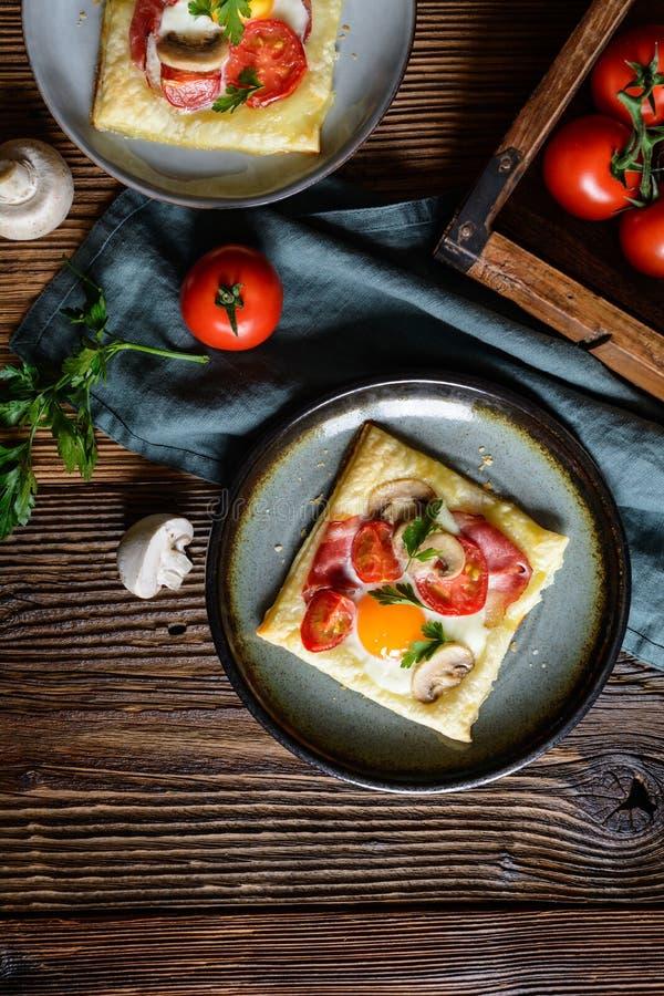 Empanadas de la pasta de hojaldre con el huevo, el tocino, las setas y el tomate imagenes de archivo