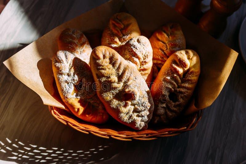 Empanadas dulces hermosas con las manzanas en azúcar en polvo en luz del sol directa en una cesta fotografía de archivo libre de regalías