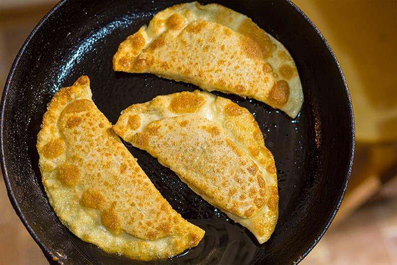Empanadas fritas deliciosas con la carne y el cheburek de los verdes en una cacerola con aceite imagen de archivo libre de regalías