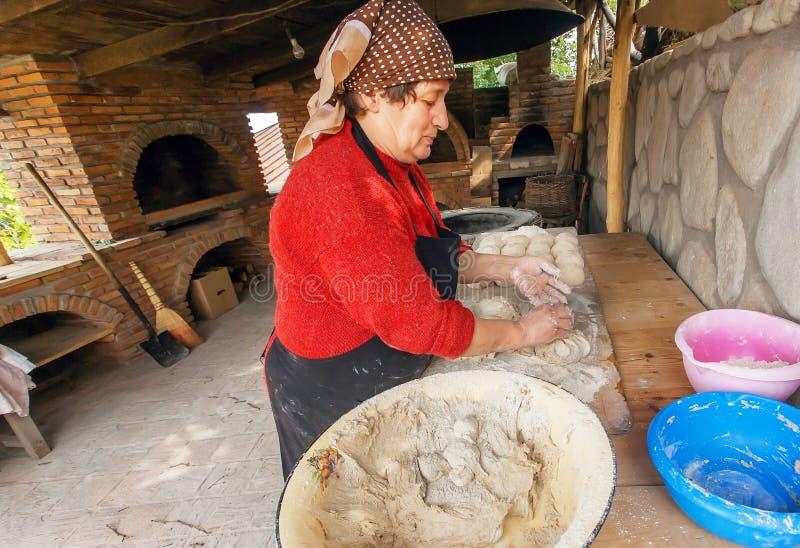 Empanadas mayores de la hornada de la mujer en su cocina casera en el estilo georgiano del pueblo con el horno de piedra imágenes de archivo libres de regalías