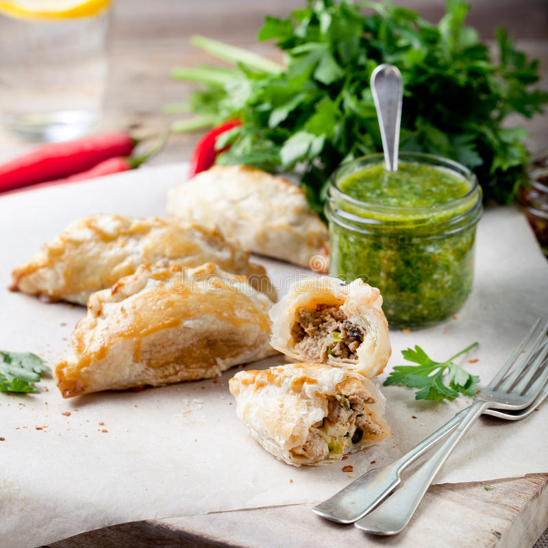 Empanadas with meat and green chili sauce. Traditional mexican dish. Empanadas with ground meat and green chili sauce. Traditional mexican dish stock image