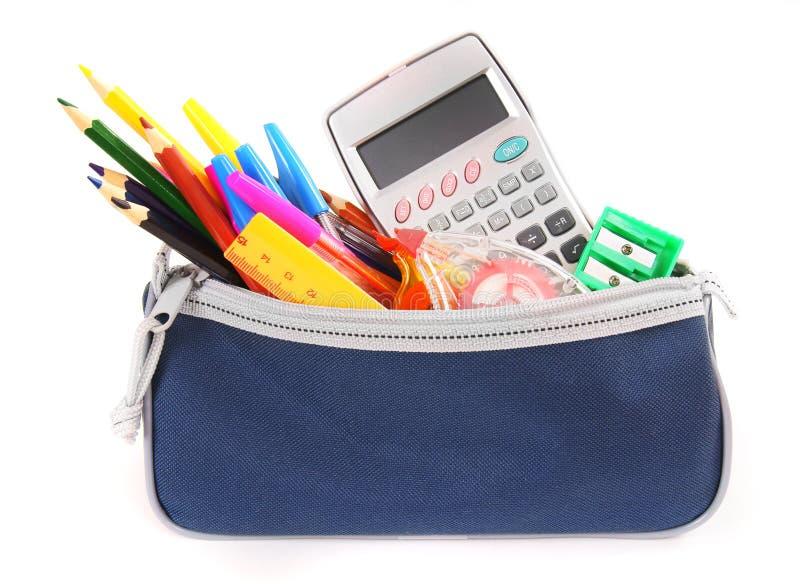 Empaquete con las herramientas de la escuela en un fondo blanco foto de archivo