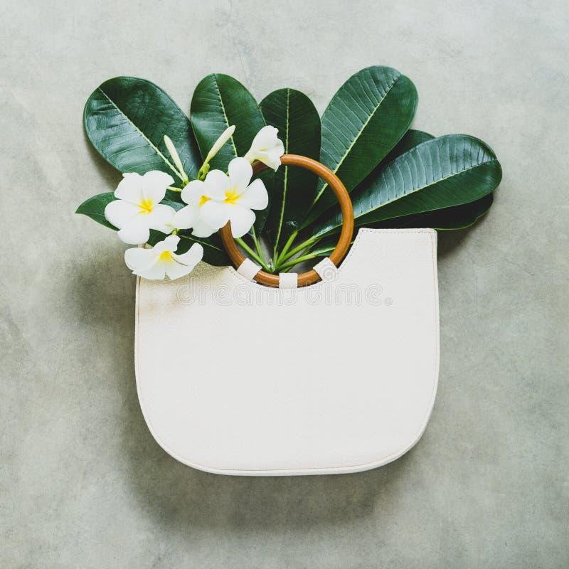 Empaquete con las manijas de madera y el plumeria blanco o las flores y las hojas del frangipani en el fondo de piedra cuadrado fotografía de archivo libre de regalías