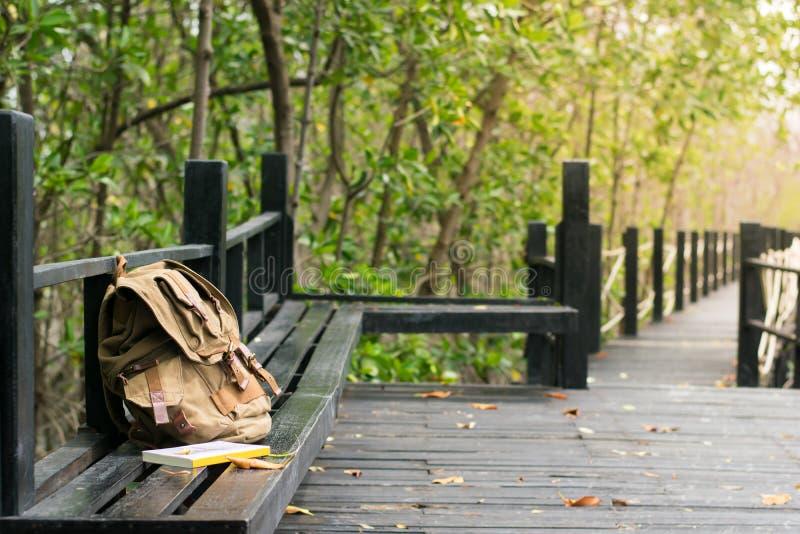 Empaquete el paquete y un libro en la silla en parque imagen de archivo