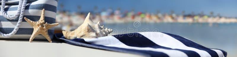 Empaquete en la playa con las estrellas de mar, la cáscara y la toalla azul imagen de archivo
