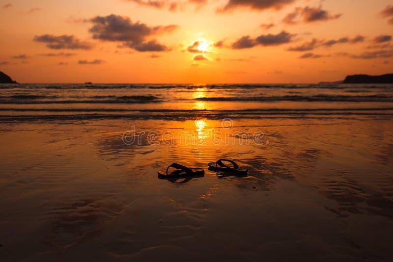 Emparéjese de chancletas en la puesta del sol, tiempo de la salida del sol en la playa fotografía de archivo