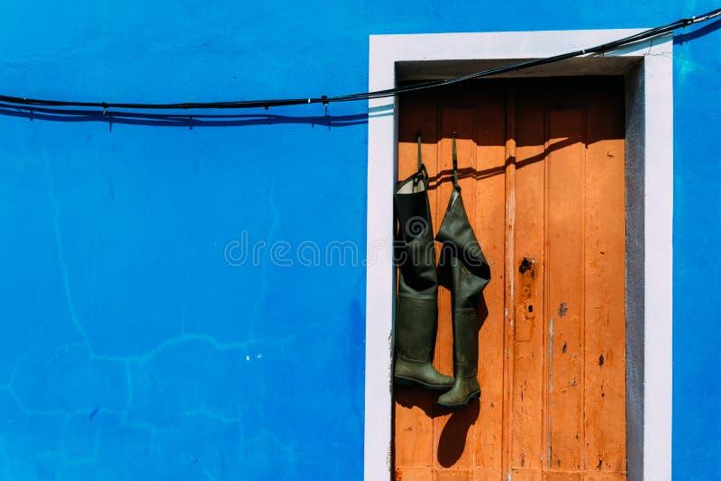 Emparéjese de los wellies que cuelgan de la entrada rústica marrón con el espacio azul brillante de la copia de la fachada de la  foto de archivo libre de regalías