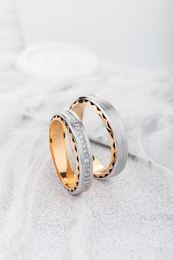 Emparéjese del anillo de bodas del oro de dos tonos con la superficie mate y de diamantes en el fondo brillante blanco foto de archivo