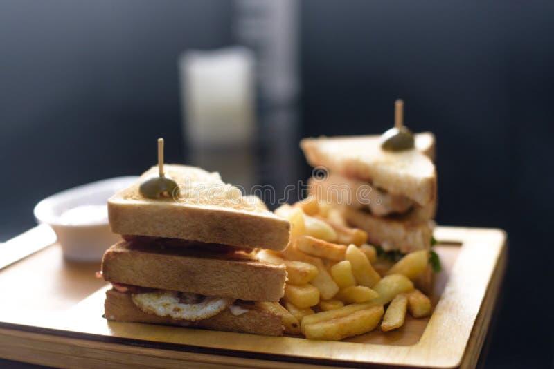 Emparedado de club del pollo en una placa blanca con las patatas fritas picantes imagenes de archivo