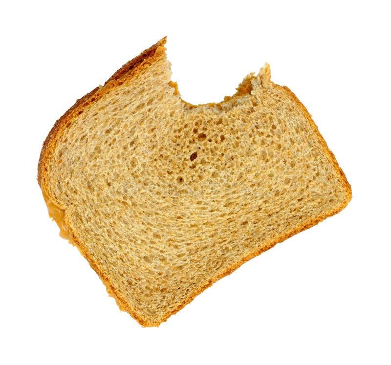 Emparedado mordido de la mantequilla de cacahuete en el fondo blanco imagenes de archivo