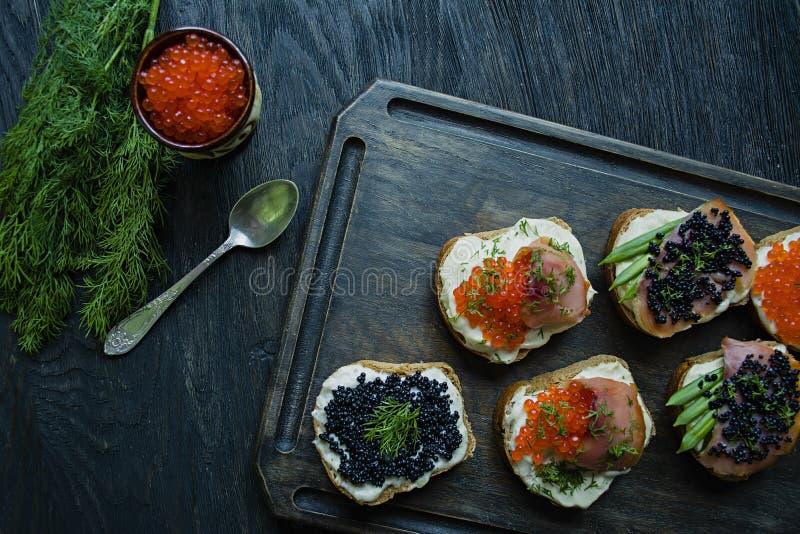 Emparedados con el caviar rojo y negro Primer Fondo de madera oscuro fotos de archivo
