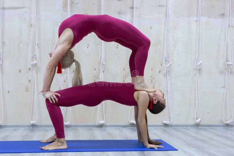 Emparelhe as mulheres desportivas da ioga que fazem o exercício no fundo à moda cinzento Pose da ioga dos pares imagens de stock