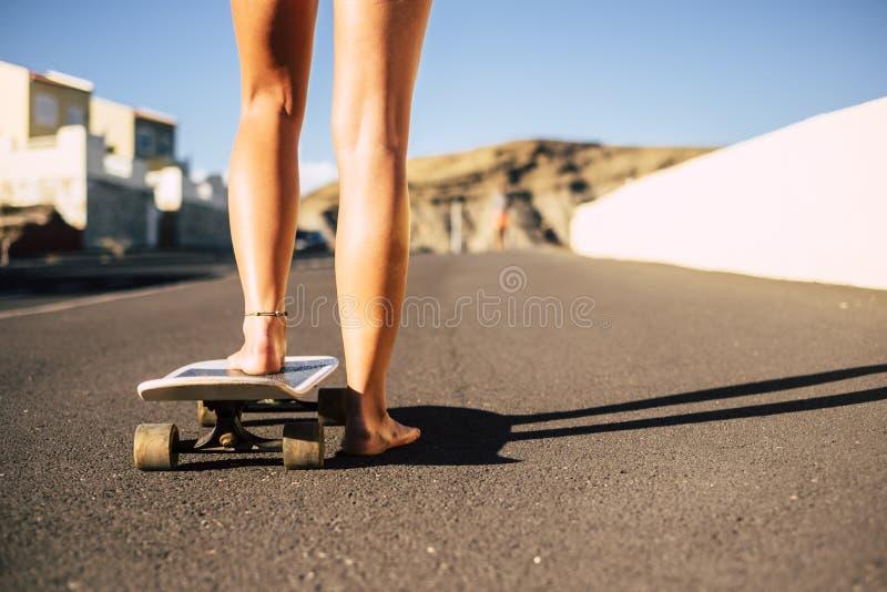 Emparelhe da jovem mulher dos pés com os pés descalços pronta para começar com o skate no asfalto dia ensolarado das férias e da  fotografia de stock