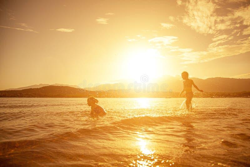 Emparelhe das crianças que jogam no mar, tiro tomado no por do sol imagem de stock royalty free