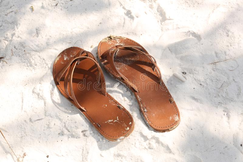 Emparelhe das sandálias na areia imagens de stock royalty free