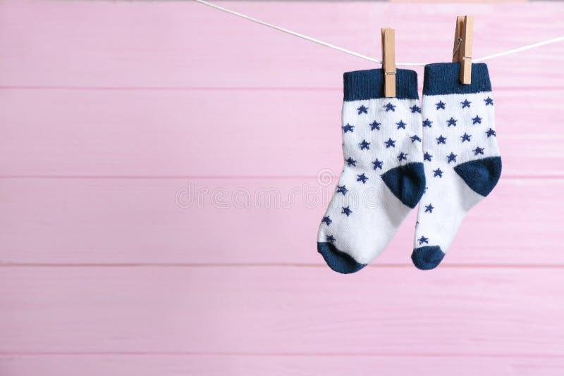 Emparelhe de peúgas na linha da lavanderia contra o fundo de madeira cor-de-rosa Acess?rios do beb? fotos de stock royalty free