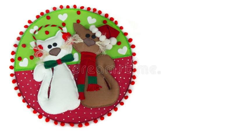 Emparelhe dos gatos feitos na espuma com a decoração do Natal em um círculo de vermelho e de verde com os corações brancos imagem de stock