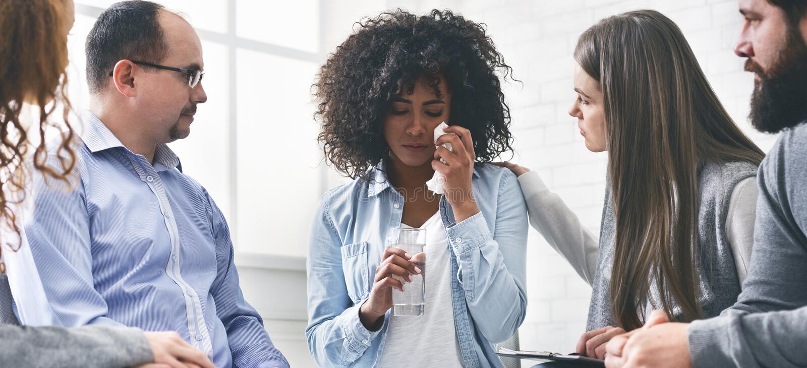 Therapy Session Group Members Comforting Crying Woman, Giving Glass Of Water stock photo