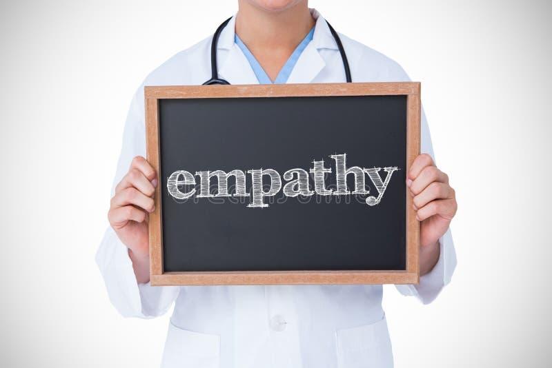 Empatia przeciw lekarce pokazuje małego blackboard fotografia stock