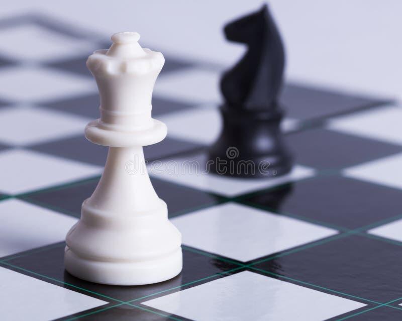 Empeño blanco y caballero negro en tablero de ajedrez imagen de archivo