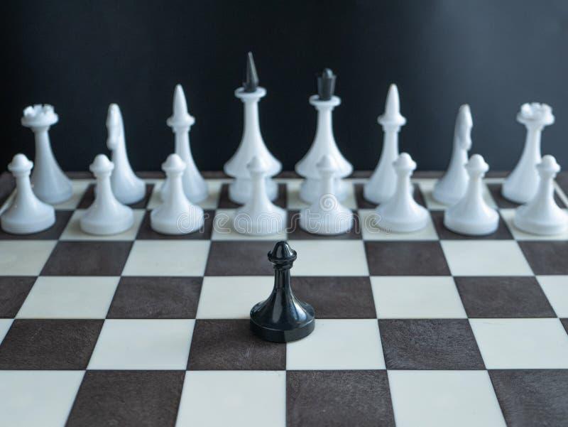 Empeño negro solo que se opone solamente al ejército entero de figuras blancas en tablero de ajedrez el concepto representa a un  fotografía de archivo libre de regalías