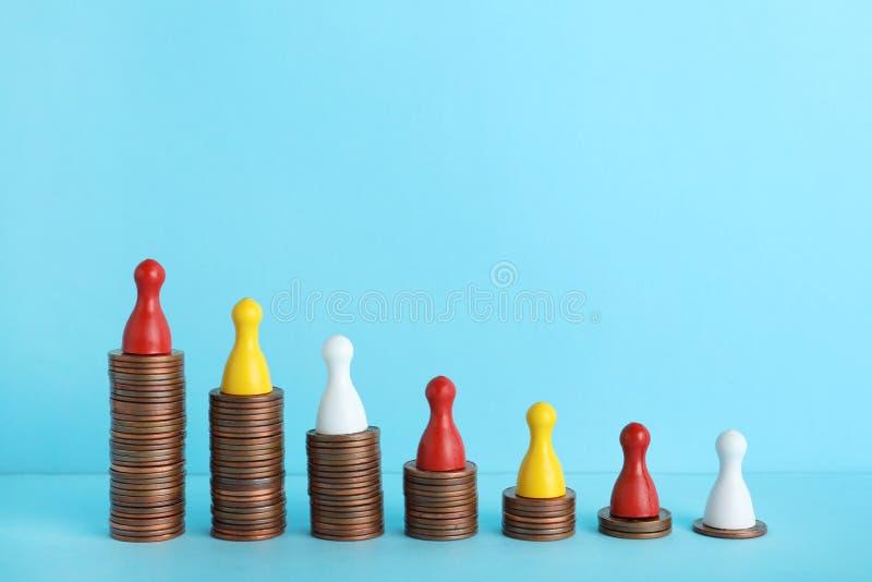 Empeños multicolores que se oponen en pilas de la moneda al fondo del color, espacio para el texto imagen de archivo libre de regalías