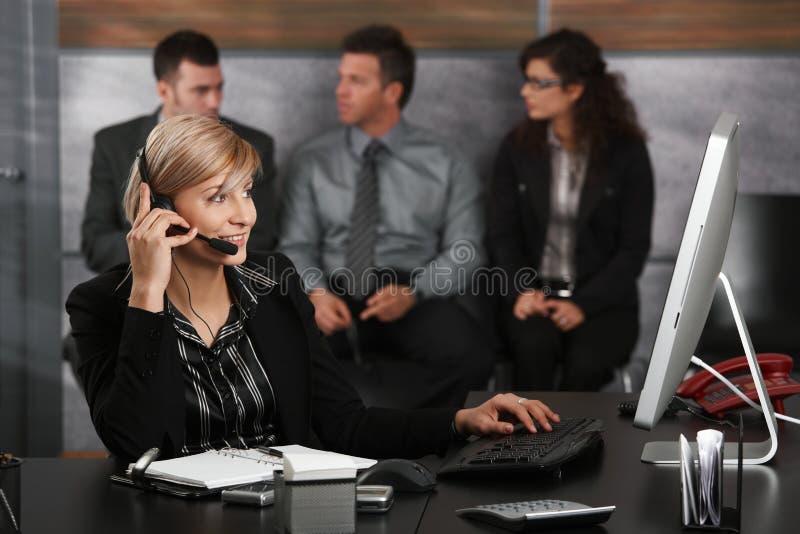 Empfangsdame, die am Telefon spricht lizenzfreies stockbild