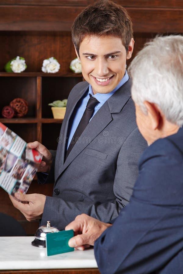 Empfangsdame im Hotel, das dem Gast Broschüre gibt stockfoto