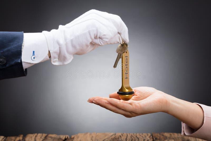 Empfangsdamen-Giving Hotel Door-Schlüssel zum Kunden stockfoto