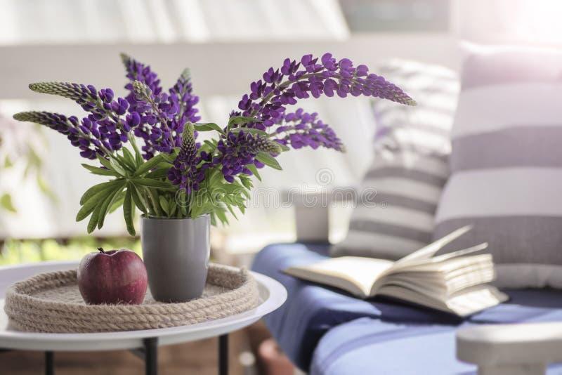 Empfindliche Zusammensetzung mit purpurrotem Lupinesblumenstrauß, -apfel und -buch lizenzfreie stockbilder