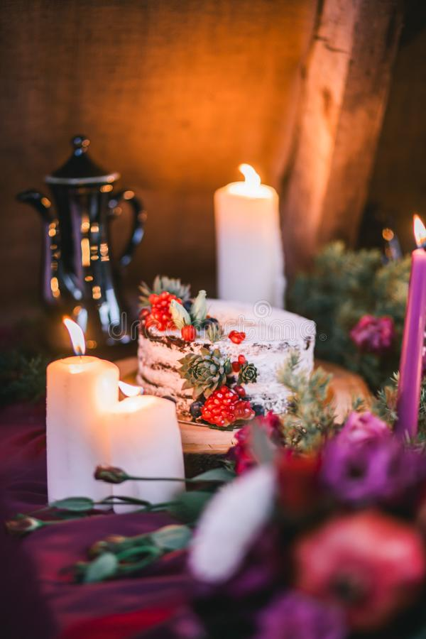 Empfindlicher heiratender weißer Kuchen verziert mit Granatapfel und saftiges umgeben durch Blumen und Kerzen lizenzfreies stockfoto